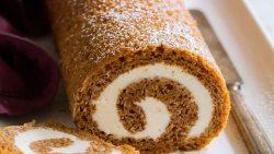 Rollo de calabaza en un plato blanco con una rodaja cortada para mostrar el relleno de queso crema en espiral.