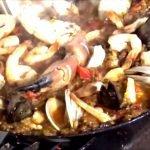 Paella de mariscos en una sartén de acero al carbono Lodge cocinada a fuego abierto
